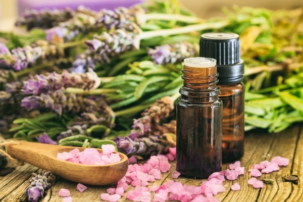 Fresh lavender bunch, essential oil and bath salt on wooden background