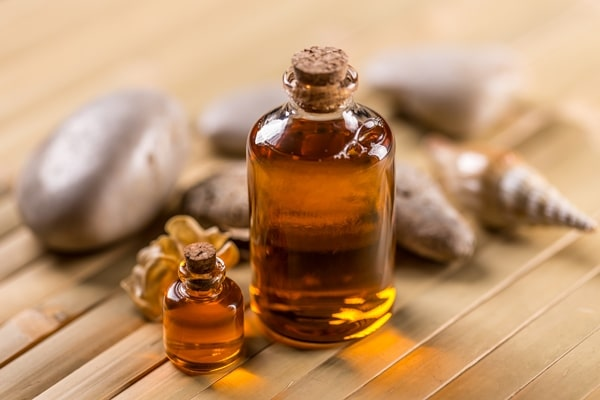 Bottles with aroma oil on bamboo background