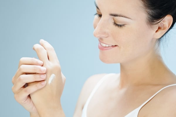 Woman applying skin product on her hands