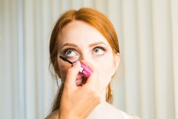 Assistant applying castor oil eyelash growth serum on eyelashes of a woman