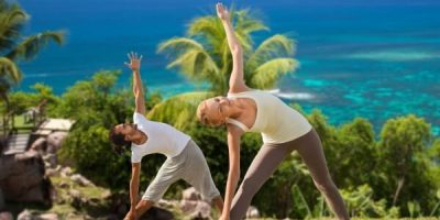 Male and female couple doing yoga outdoors