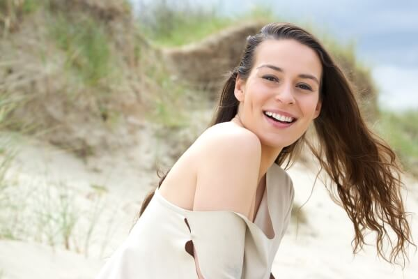Beautiful woman smiling; her hair blown by the wind
