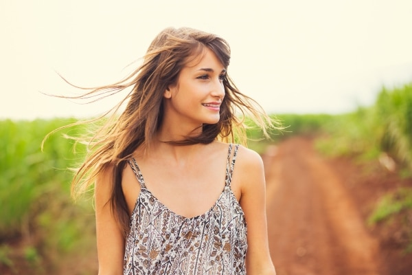 Girl outdoors with healthy hair blown by the wind