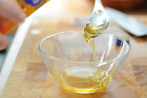 Puring argan oil into a bowl with a spoon