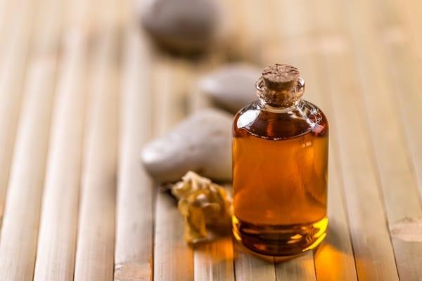 Bottle of jojoba oil on bamboo surface