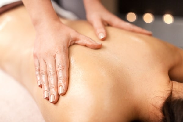 A massage therapist giving a woman a back massage